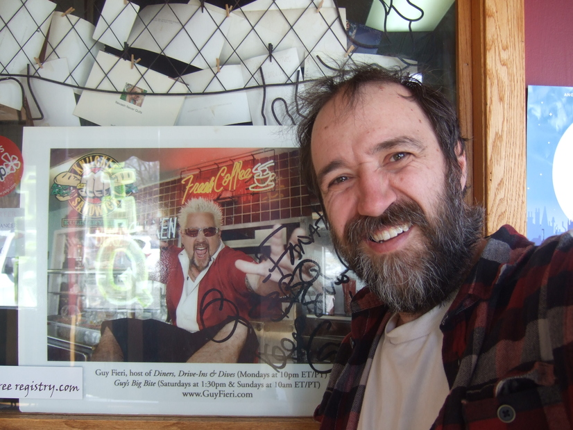 The author, a bearded man in a plaid shirt, smiling at the camera, standing next to a photo of Guy Fieri from Diners, Drive-Ins, and Dives.